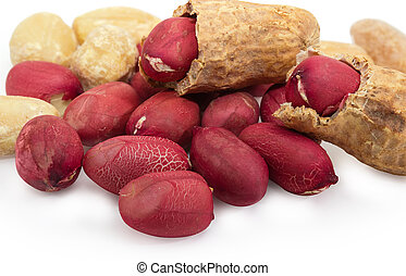 Pile of partly peeled roasted peanuts close-up