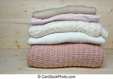 Pile of pink and white woolen sweaters
