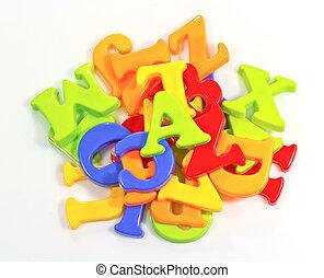 Pile of Plastic Alphabets on White Background