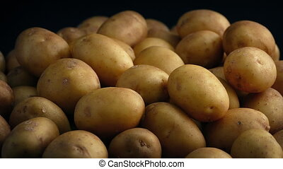 Pile Of Potatoes On Black Background - Pile of potatoes...