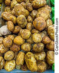 Pile of potatoes selling at farmer's market vendor - Pile of...
