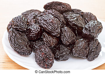 Pile of prunes on a white plate