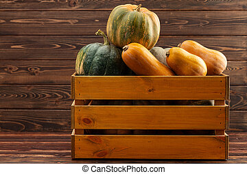 Pile of pumpkins in a wooden box