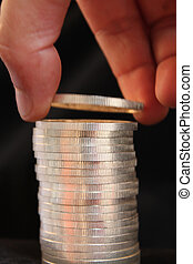 pile of pure silver coins and hand adding or taking one