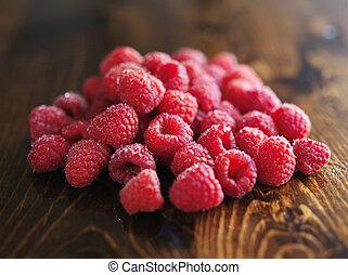 pile of raspberries on wooden table,