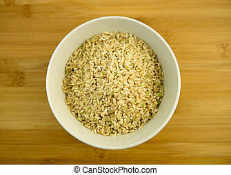 Pile of raw brown rice in a white bowl