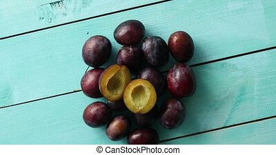Pile of ripe plums on blue wood - From above shot of...