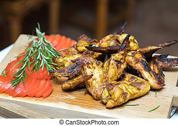 Pile of roasted grilled chicken wings on oak wooden board. -...