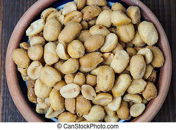 roasted peanuts - pile of roasted peanuts in a bowl