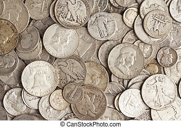 A pile of old silver coins with different prints.