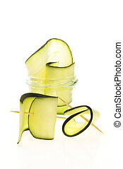 Pile of sliced zucchini pieces arranged on white background