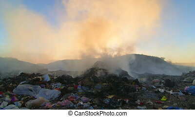 Pile of smoking garbage in the dump site