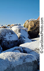 pile of snowy rocks in the winter mountains on a sunny winter day with a blue sky.