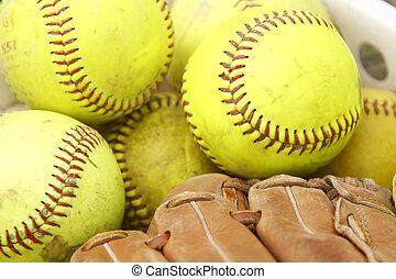 Pile of softballs and baseball glove.