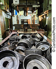 pile of stamped thick sheet black metal round parts after a hood operation in front of old blurred forming press with die tooling