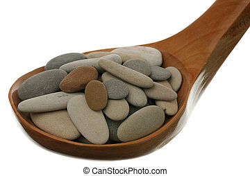 Pile of stones in a wooden spoon over white