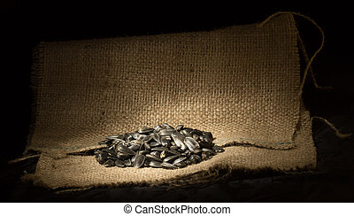 pile of sunflower seeds in the small sack on the black...