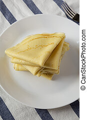 Pile of tasty blini on a white plate, low angle view. Closeup.