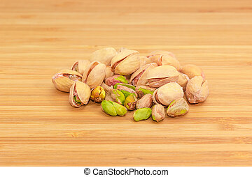 Pile of the partly peeled roasted salted pistachio nuts