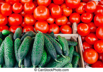Pile of tomatoes and cucumber on the market. Close
