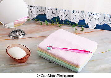 Pile of towels and toothbrush