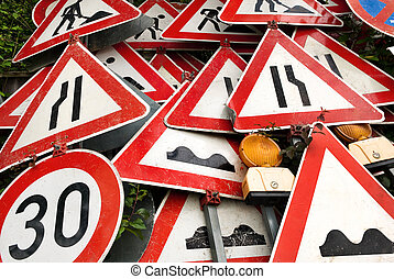 Pile of out-of-order red and white traffic signs