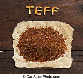 Pile of uncooked teff grain with wooden word
