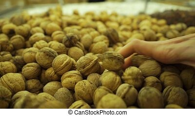 Pile of unshelled walnuts and woman hand with beautiful nail...