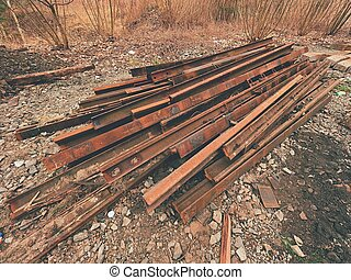 Pile of used rusty rails. Stock of steel rails at old closed railway station.  Metal material