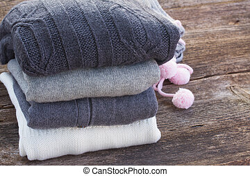 woolen clothes - pile of warm woolen clothes on wooden table...