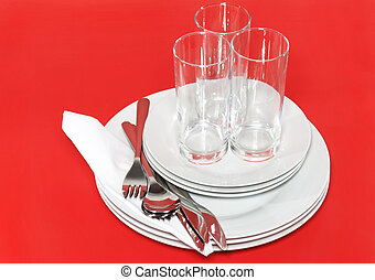 Pile of white plates, glasses, forks, spoons.