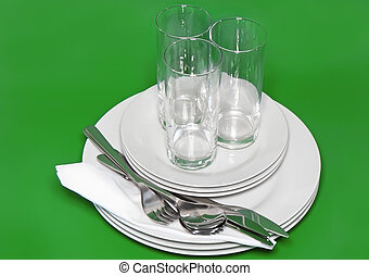 Pile of white plates, glasses, forks, spoons.