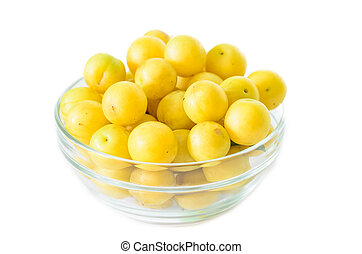 pile of yellow mirabelle plums in bowl isolated on white...