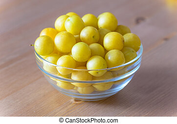 pile of yellow mirabelle plums in bowl on wooden table -...