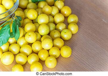 pile of yellow mirabelle plums on wooden table - stock photo