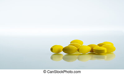 Pile of yellow oval tablet pills on white background with copy space for text. Mild to moderate pain management. Pain killer medicine. Medicine for relieve high fever.