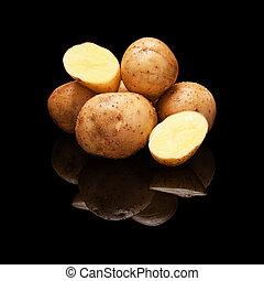 Pile of yellow potatoes isolated on black