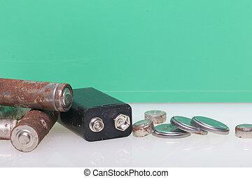 piles, de, corrosion, de, divers, formes, et, sizes., ils, mensonge, dispersé, sur, a, surface blanche, sur, a, vert, arrière-plan., protection environnement, recyclage, de, utilisé, batteries.
