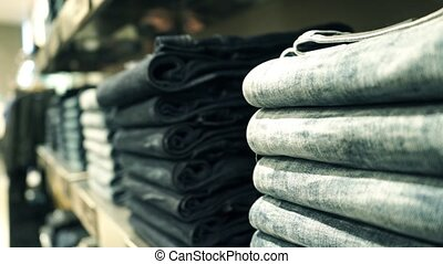 Piles of new jeans in the store pan close up video