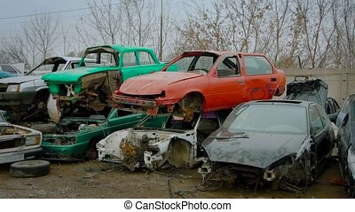 Piles of old broken rusty cars on wrecking yard. Stacked...