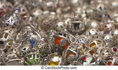 A pile of intricate silver ornaments with colored marbles inside