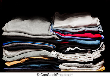 PIles of various clothes from laundry in a wardrobe. Black...