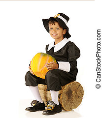 An adorable preschool-aged Pilgrim boy holding a pumpkin while sitting on an old log. On a white background.