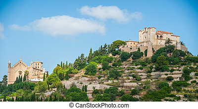 Pilgrimage church of Sant Salvador on green hill in Arta village, Mallorca island, Spain. Beautiful landsacape with medieval architecture, green trees and blue sky with clouds on a sunny day.