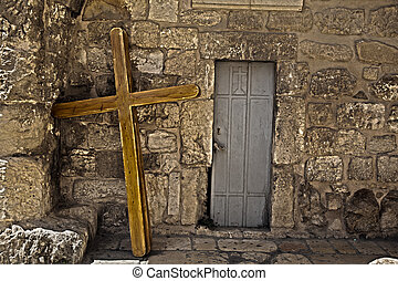 Three large scaled crusifixes resting on the wall of the Church of the Holy Sepulchre. These crusifixes are used by pilgrims who carry them along the Via Dolorosa, reenacting the path Jesus Christ made on his way to his own crusifixion with a similar crusifix on his back.