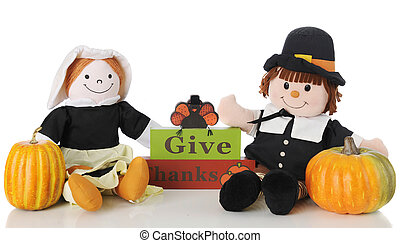 """Two happy pilgrim dolls sitting by a """"Give Thanks"""" sign topped with a turkey. On a white background."""