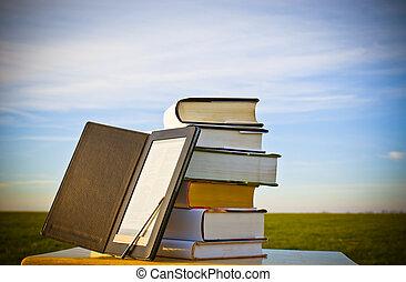 pilha livros, com, ebook, leitor, ao ar livre, deitando,...