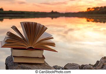 pilha livros, e, abertos, livro capa dura, ligado, obscurecido, paisagem natureza, fundo, contra, céu ocaso, com, light., espaço cópia, costas, para, school., educação, experiência.