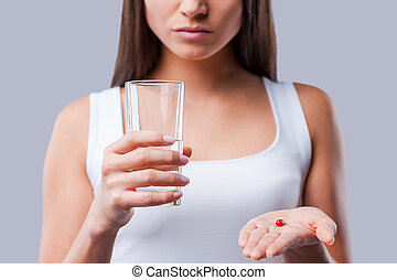 Pill in her hand. Cropped picture of young woman holding a glass with water and pills in her hands