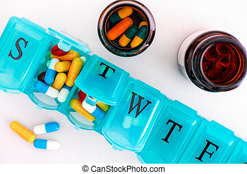 Pill organizer with pills and bottles on white background.